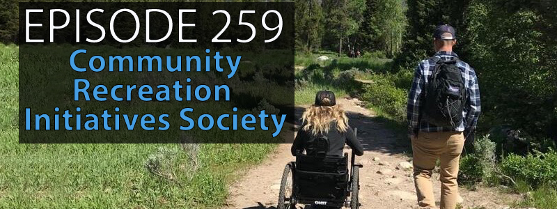 Image of a hiking trail with one able bodies person and one person in an adapted wheelchair hiking through a lush green set of trees.